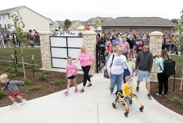 Picture of the grand opening of the all play inclusive park in Cedar Falls with over 500 people showing up and walking through the gate.